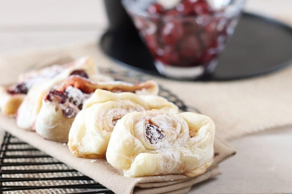 Süße Blätterteigschnecken mit Kirschen und Pudding